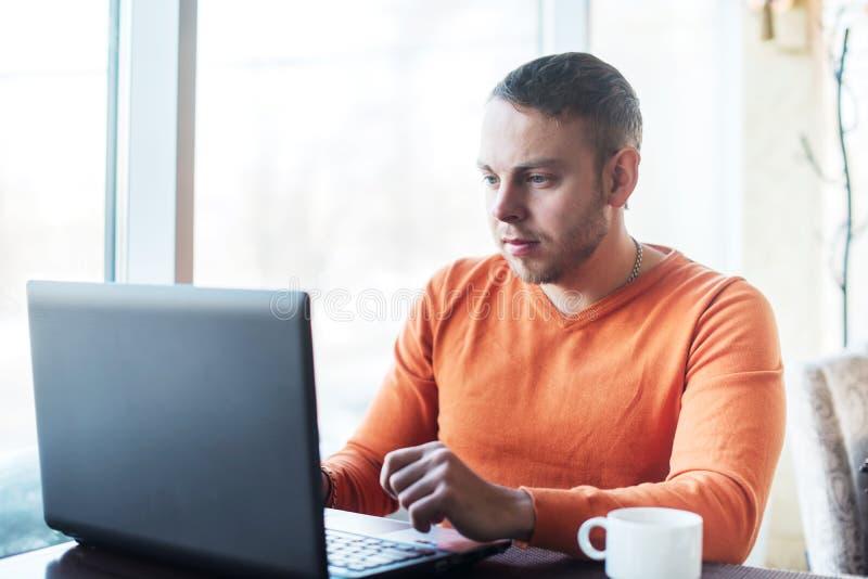 Man som arbetar på anteckningsboken i kafé arkivbilder