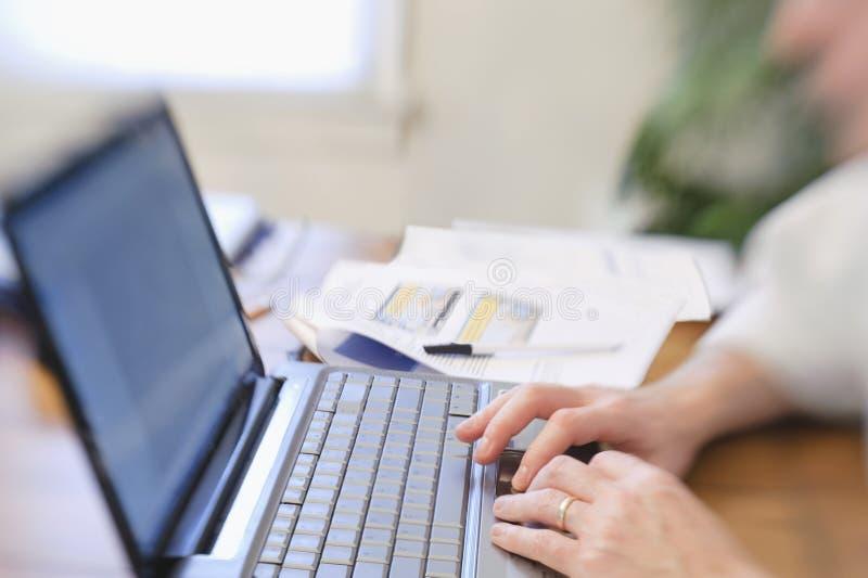 Man som arbetar på bärbar datorhänder på datortangentbordet fotografering för bildbyråer