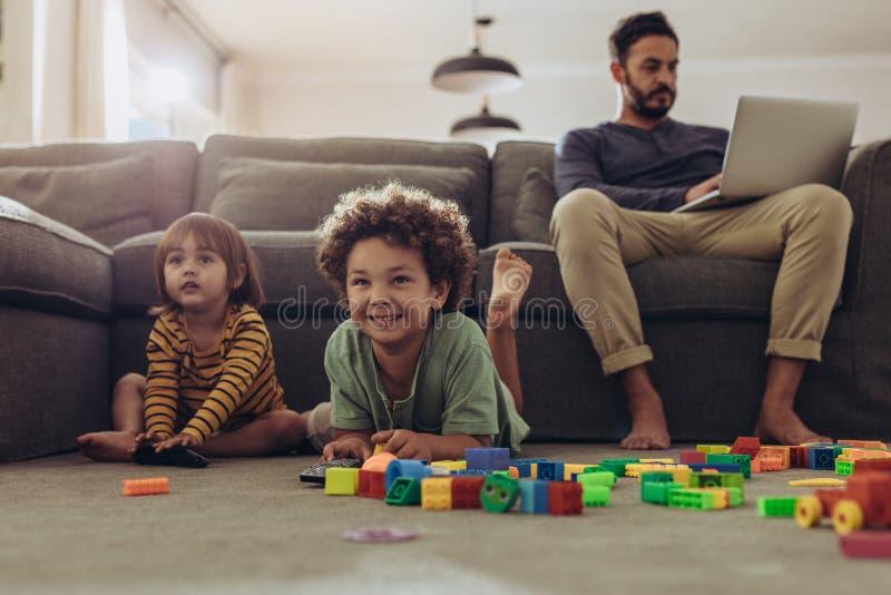 Man som arbetar på bärbara datorn som hemma sitter med ungar som spelar på fet arkivfoto