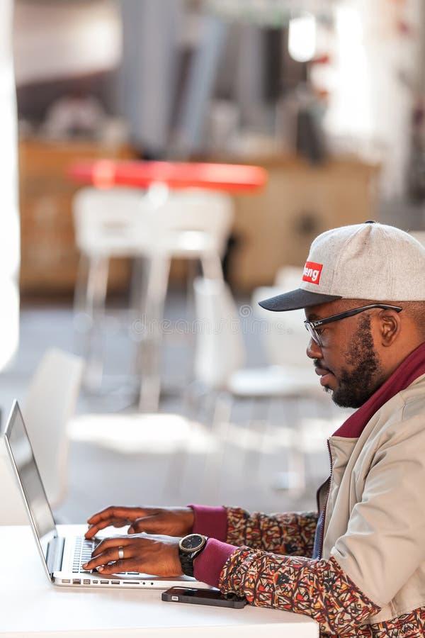 Man som arbetar på bärbara datorn i kafé royaltyfri fotografi