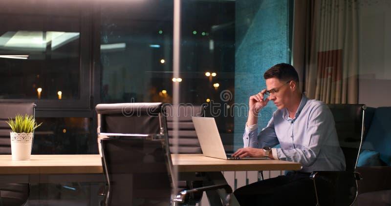 Man som arbetar på bärbara datorn i mörkt kontor royaltyfri bild