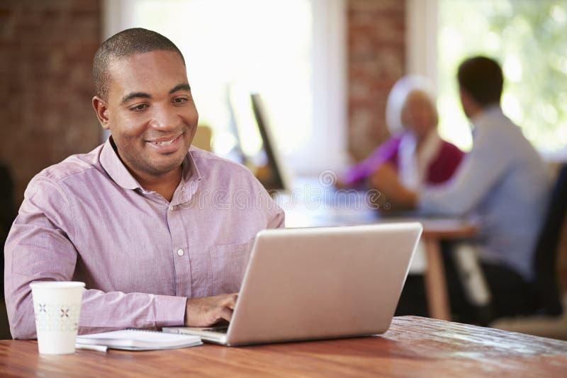 Man som arbetar på bärbara datorn i modernt kontor royaltyfria bilder