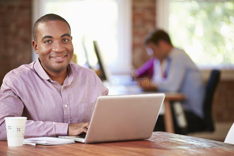 Man som arbetar på bärbara datorn i modernt kontor arkivbild