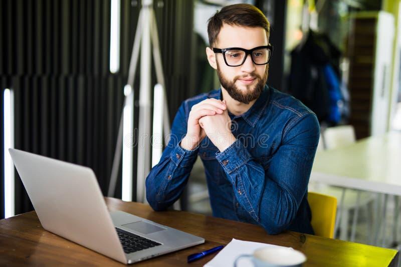 Man som arbetar på bärbara datorn i modernt kontor Se på sida fotografering för bildbyråer