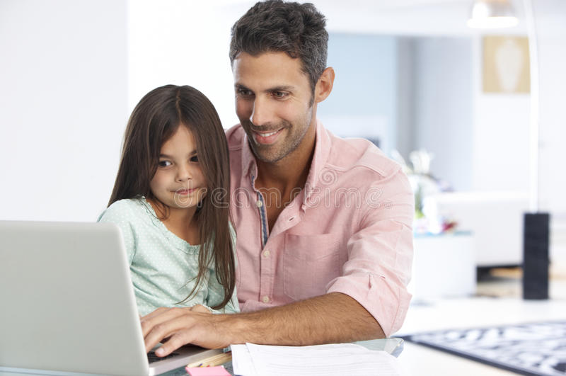 Man som arbetar på bärbara datorn med dottern i inrikesdepartementet arkivfoton