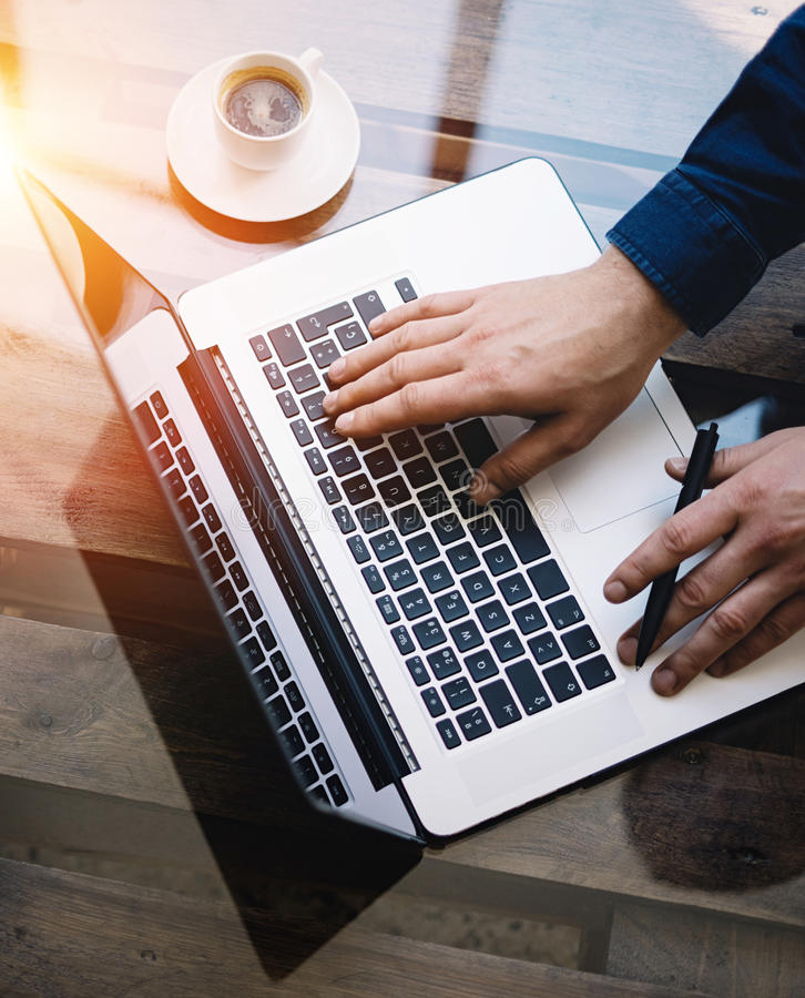 Man som arbetar på bärbara datorn på det soliga kontoret Manlig handmaskinskrivning på tangentbordet Modern anteckningsbok, kopp  royaltyfria bilder