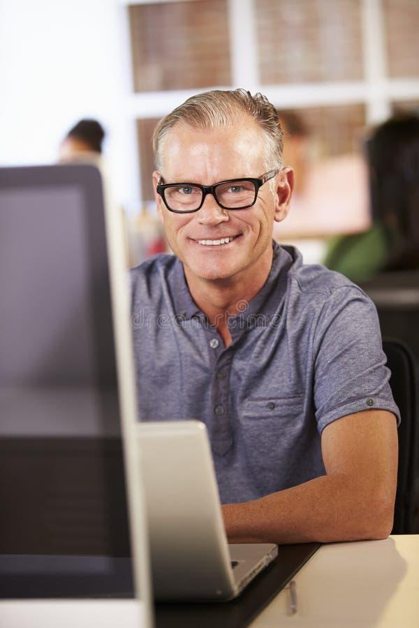 Man som arbetar på datoren i modernt kontor arkivfoto