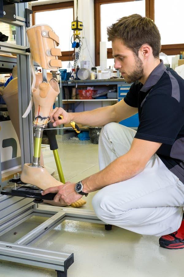 Man som arbetar på den prosthetic benenheten royaltyfria foton