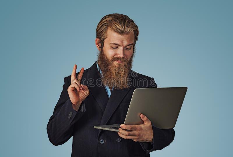 Man som arbetar på en bärbar dator som ger gest för fredsegerhand royaltyfria bilder