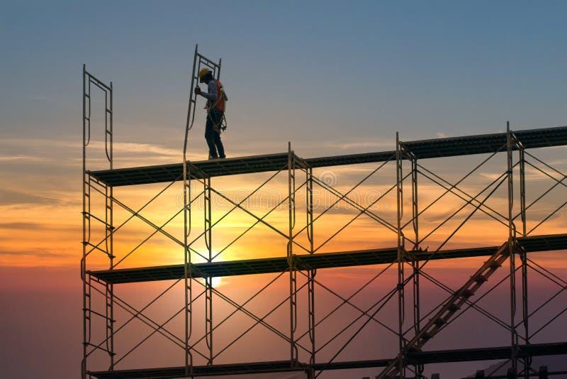 Man som arbetar på konstruktionsplats med ställningen och bygger med solnedgångbakgrund, material till byggnadsställning för kons arkivfoton