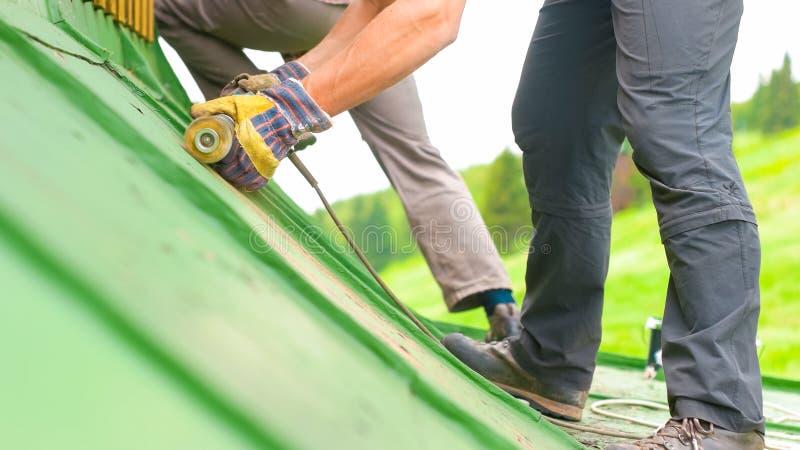 Man som arbetar på taket, Sandering målarfärg arkivfoto