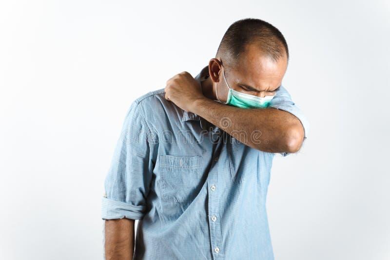 Man som bär ansiktsmask nysningar eller hosta i armbågen för att förhindra spridning av viruset COVID-19 eller Corona Virus mot v royaltyfria foton