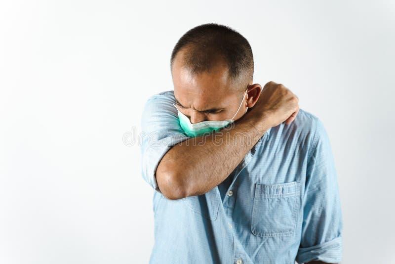 Man som bär ansiktsmask nysningar eller hosta i armbågen för att förhindra spridning av viruset COVID-19 eller Corona Virus mot v arkivfoto
