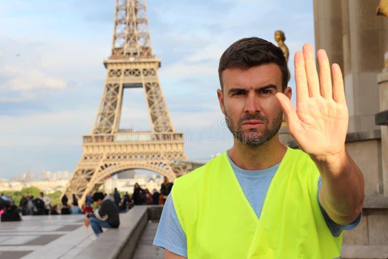 Man som bär den gula västen som protesterar i Paris, Frankrike arkivfoton