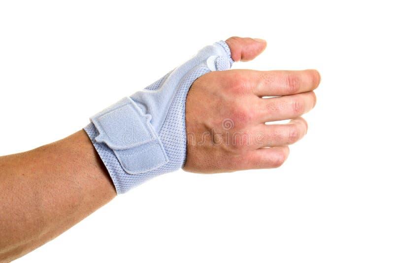 Man som bär det understöda staget på handleden och handen arkivbild