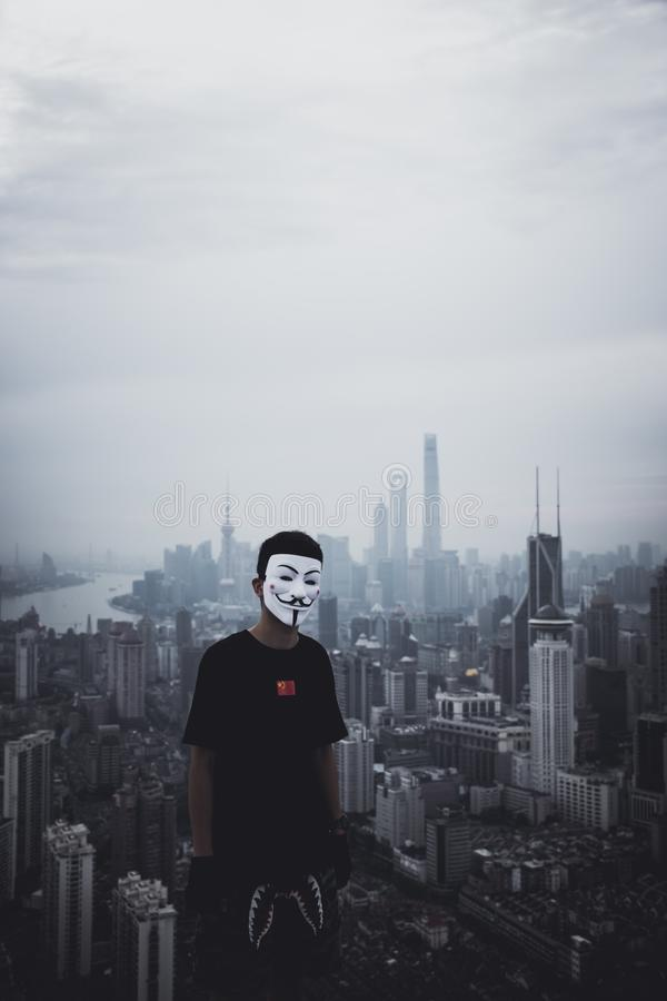 Man som bär en anonym maskering som står på ett tak med en fantastisk stads- stad i baksidan arkivfoton