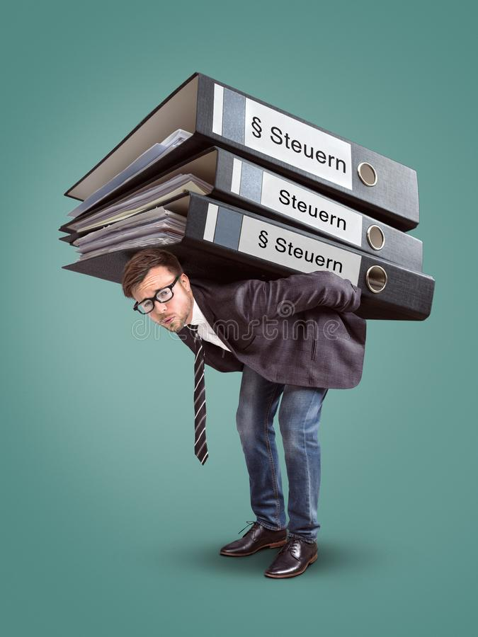 Man som bär en jätte- bunt av skattmappar arkivbild
