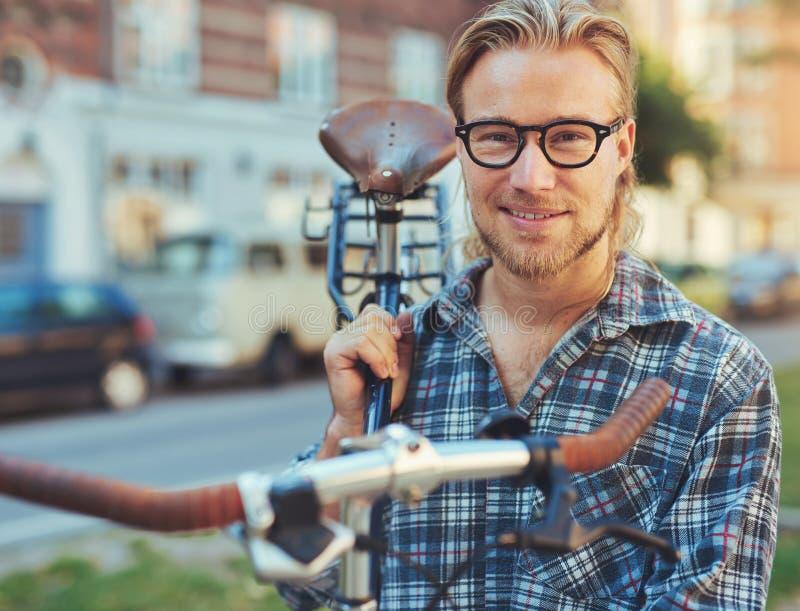 Man som bär hans cykel barn för kvinna för livsstil för bakgrundsskönhetstad stads- arkivfoton