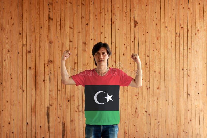 Man som bär Libyen flaggafärg av skjortan och står med den lyftta både näven på träväggbakgrunden royaltyfri bild