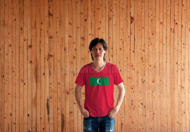 Man som bär skjortan för Maldiverna flaggafärg och står med två händer i flåsandefack på träväggbakgrunden royaltyfria bilder
