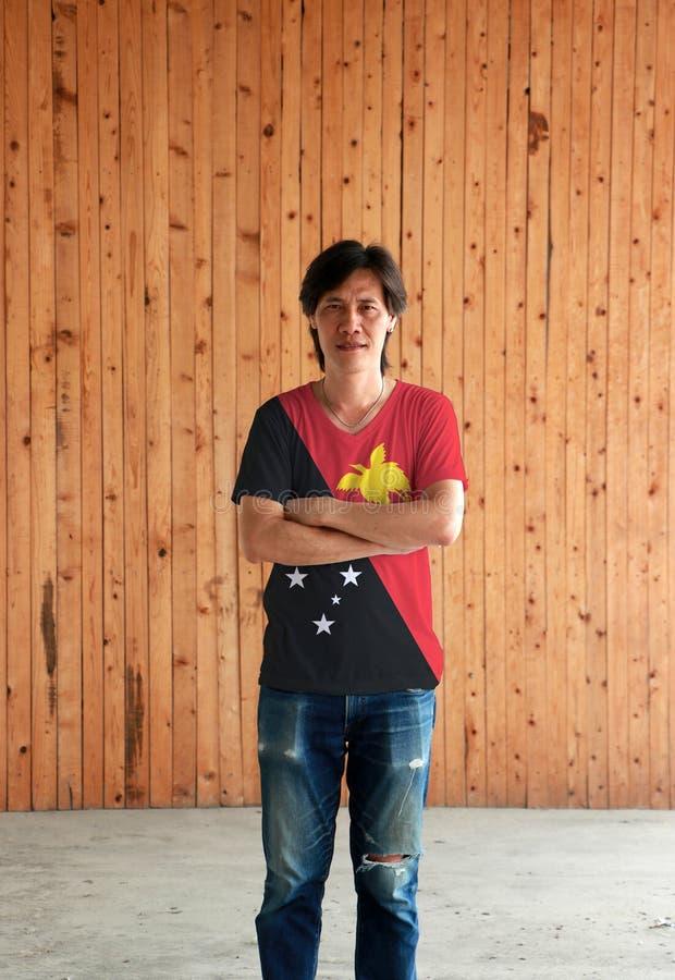 Man som bär skjortan för Papua Nya Guinea flaggafärg och att korsa ens arm på träväggbakgrund arkivfoton