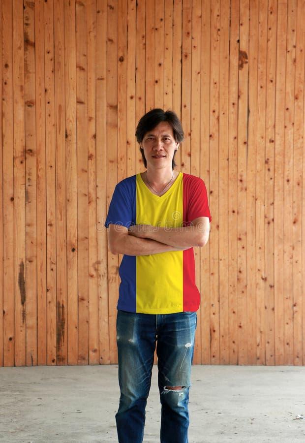 Man som bär skjortan för Rumänien flaggafärg och att korsa ens arm på träväggbakgrund arkivfoton