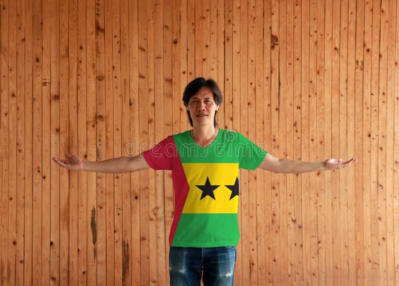 Man som bär skjortan för São Tomé och Príncipe flaggafärg och vitt som står med armar är öppna på träväggbakgrunden arkivbild