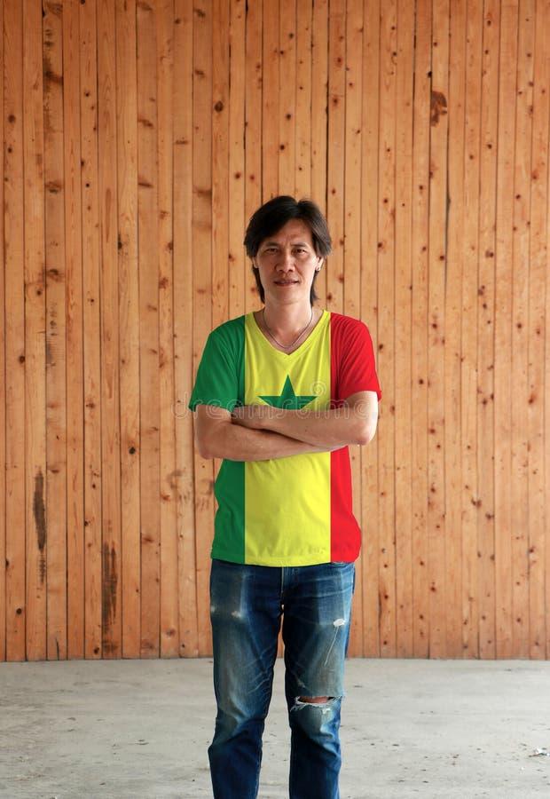 Man som bär skjortan för Senegal flaggafärg och att korsa ens arm på träväggbakgrund arkivbild