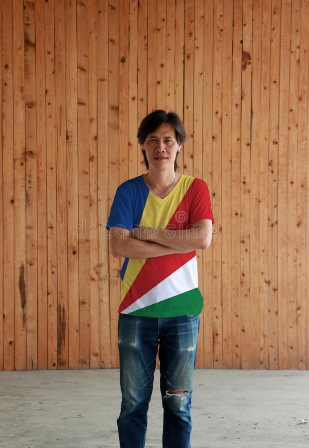 Man som bär skjortan för Seychellerna flaggafärg och att korsa ens arm på träväggbakgrund arkivbild