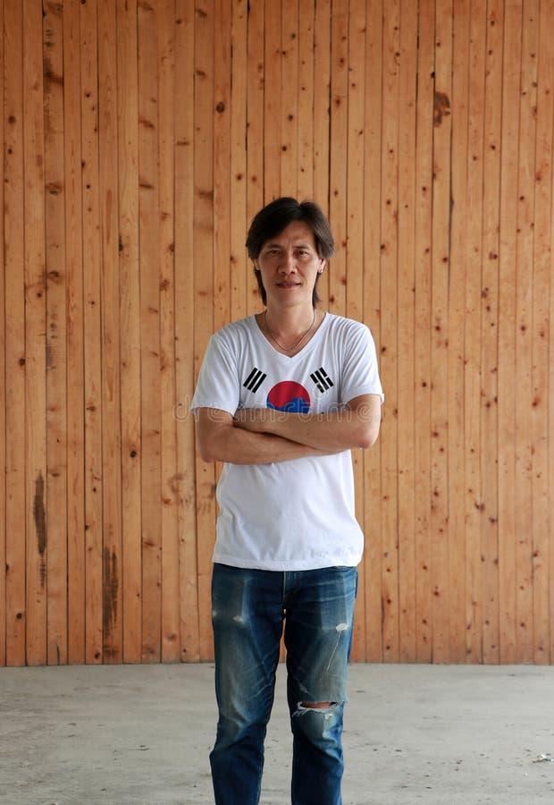 Man som bär skjortan för Sydkorea flaggafärg och att korsa ens arm på träväggbakgrund arkivfoto