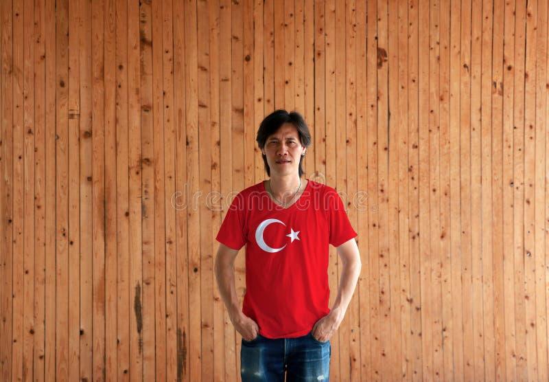 Man som bär skjortan för Turkiet flaggafärg och står med två händer i flåsandefack på träväggbakgrunden royaltyfri fotografi
