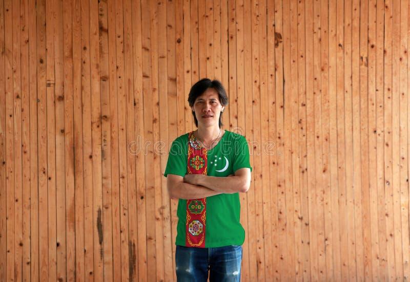 Man som bär skjortan för Turkmenistan flaggafärg och att korsa ens arm på träväggbakgrund royaltyfri bild