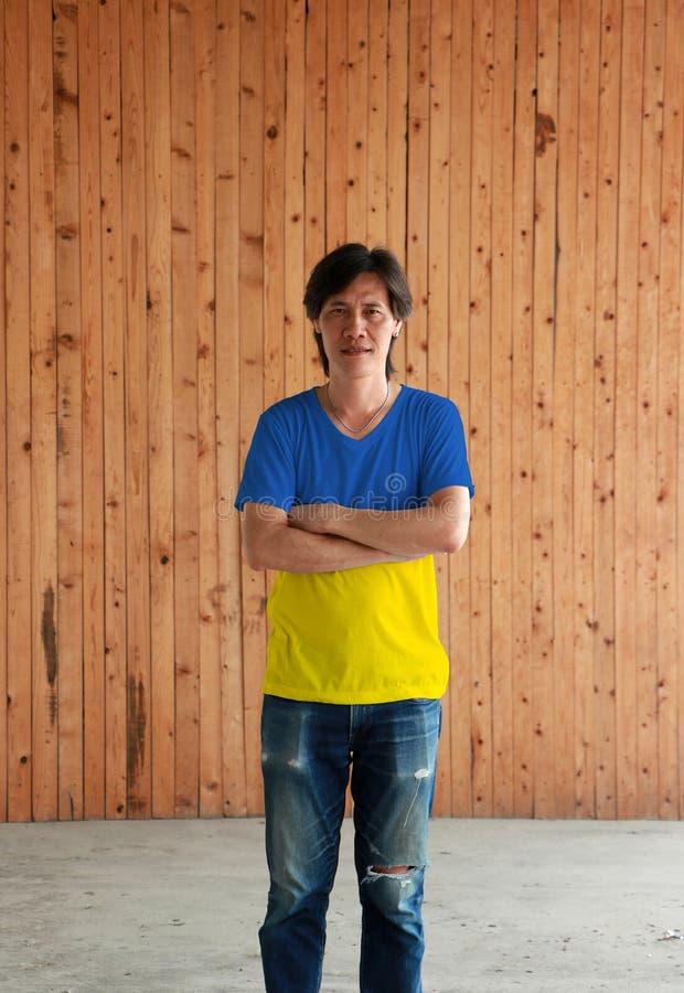 Man som bär skjortan för Ukraina flaggafärg och att korsa ens arm på träväggbakgrund arkivfoton