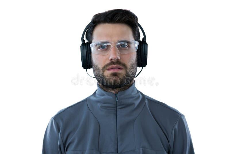 Man som bär skyddande exponeringsglas som lyssnar till hörlurar royaltyfri foto