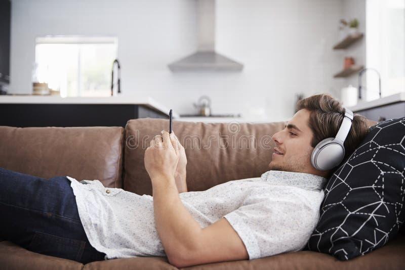 Man som bär trådlös hörlurar som ligger på den Sofa At Home Streaming From mobiltelefonen arkivfoton