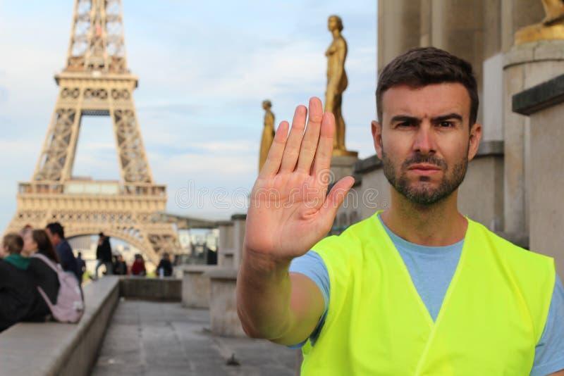 Man som b?r den gula v?sten som protesterar i Paris, Frankrike arkivfoto
