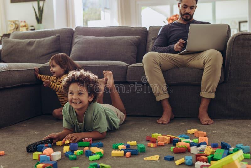 Man som babysitting hans ungar och hemifrån arbetar arkivfoton