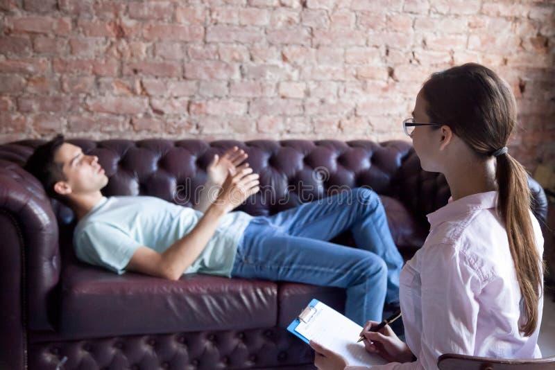 Man som berättar en psykologlägerledare om hans problem arkivbild