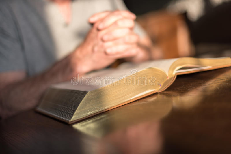 Man som ber händer på en bibel arkivfoton