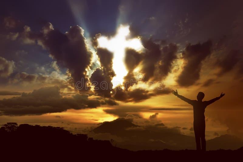 Man som ber till guden med strålen av ljus som formar korset på himlen royaltyfri foto