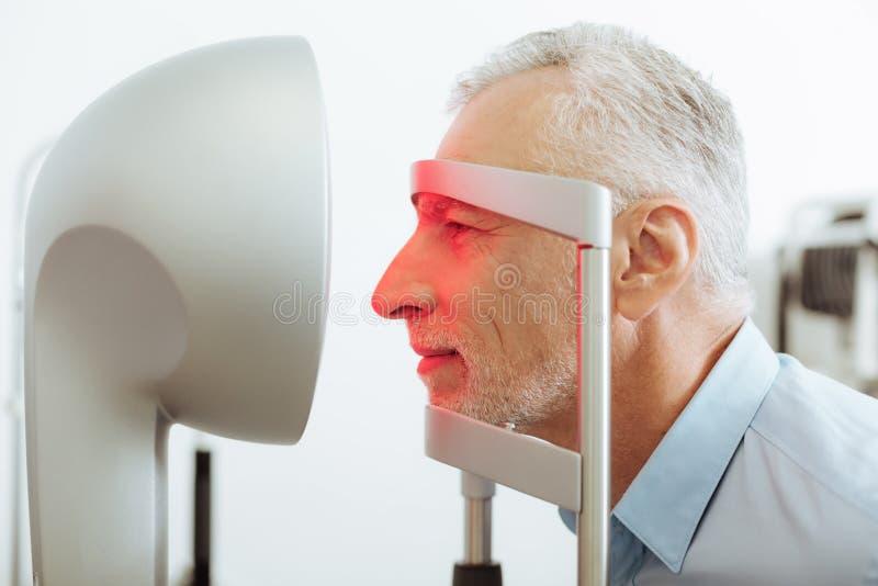 Man som besöker hans ögonläkare i morgonen royaltyfri bild
