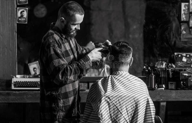 Man som bes?ker fris?ren i frisersalong Sk?ggig man i frisersalong Manfrisörfrisör som klipper hår av manligt arkivfoton