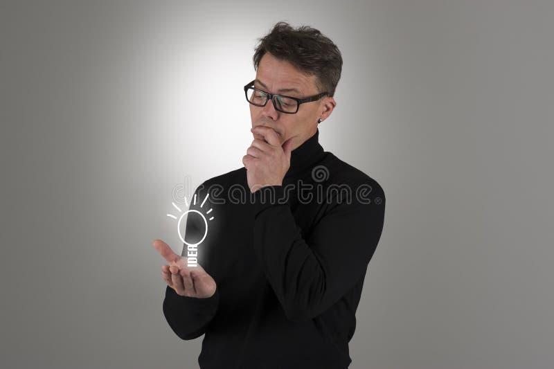 Man som beskådar en ljus idé royaltyfri foto