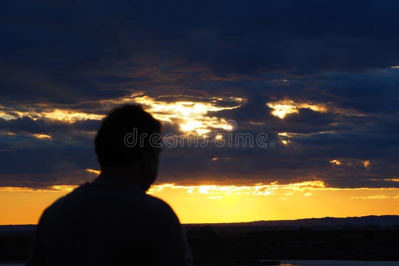 Man som beskådar solnedgångreflexionen på sjön, lerida arkivbild