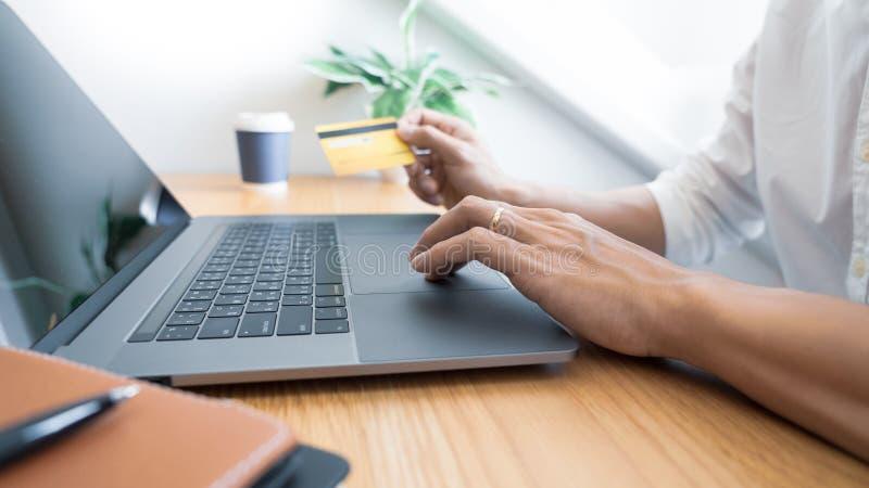 Man som betalar med kreditkorten och den skrivande in säkerhetskoden för online-shoping göra en betalning eller inhandla gods på  royaltyfri foto