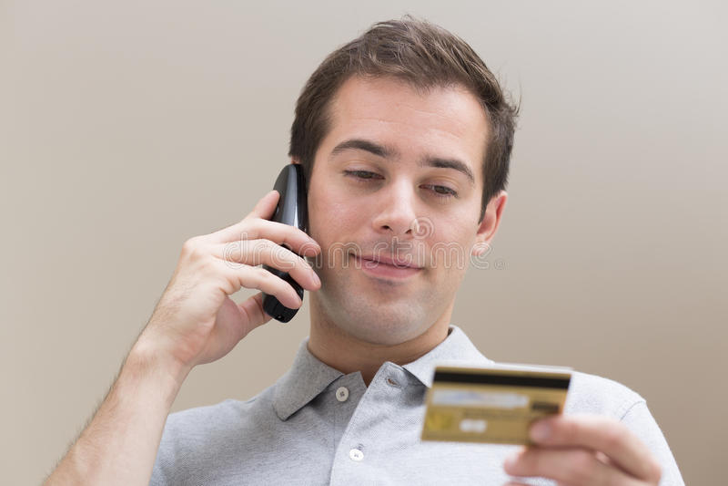 Man som betalar med kreditkorten på telefonen arkivbild