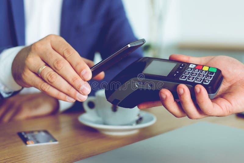 Man som betalar räkningen till och med smartphonen genom att använda NFC-teknologi i kafé arkivbilder