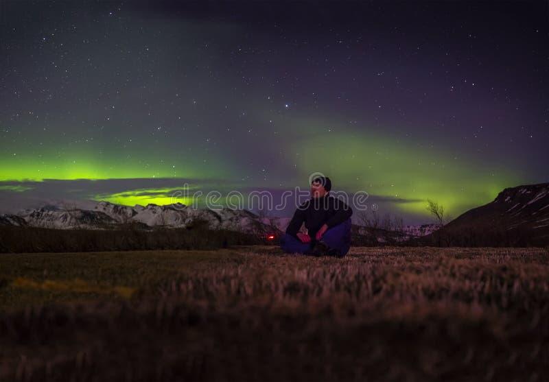 Man som beundrar morgonrodnad på natten i Island royaltyfri bild