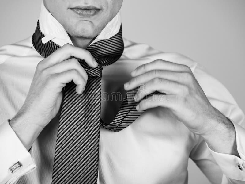 Man som binder ett randigt band i den vita skjortan royaltyfria bilder