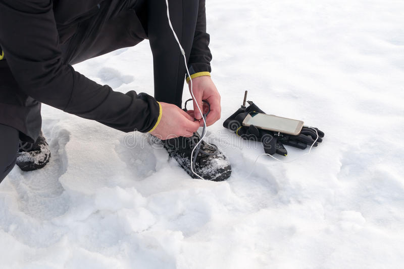 Man som binder rinnande skor på snö royaltyfri fotografi